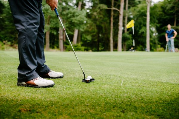 Closeup of golfer putting ball on green.