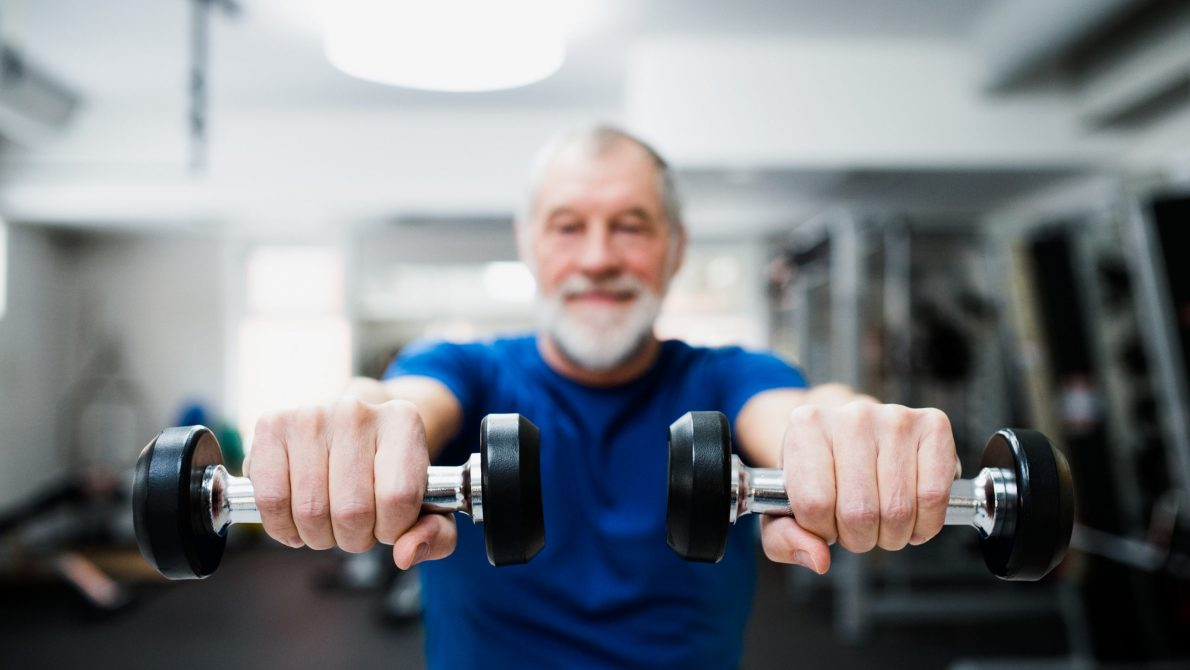 Senior man in gym working out with weights. Active Lifestyles